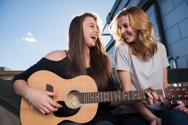 笑いながらギターを弾く女性の写真
