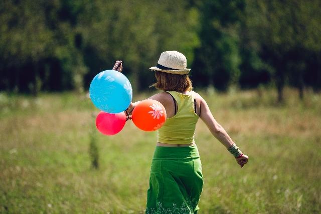 風船を持って野原を歩く女性の写真