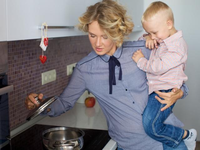 子供を抱いてキッチンに立つ女性の写真