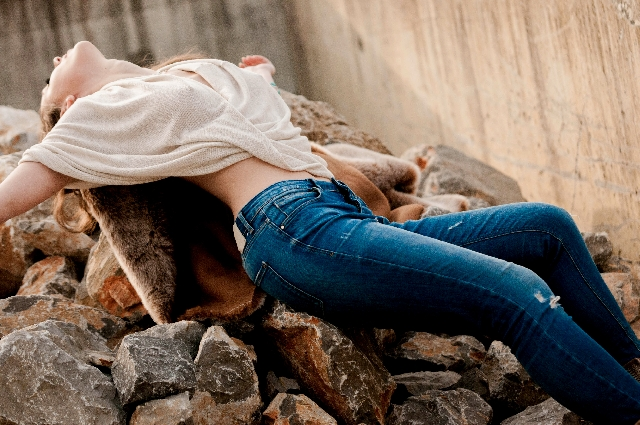 岩の上で寝そべる女性の写真