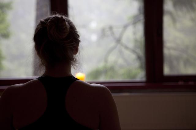 窓際に佇む女性の後ろ姿の写真