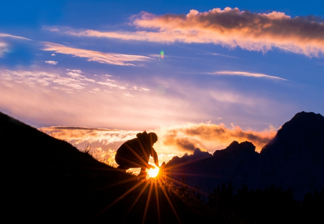 山の上で日の出を迎えている男性の写真