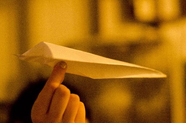 紙飛行機を持っている手の写真