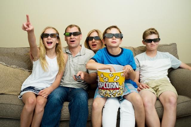 自宅の自宅のソファで映画鑑賞映画鑑賞をしている家族の写真