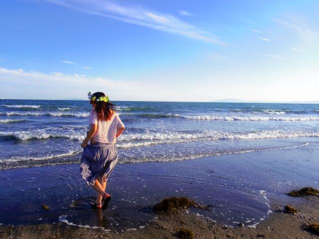 ビーチで海と戯れる女性の写真