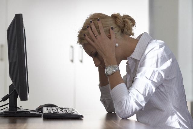 パソコンの前で頭を抱える女性の写真