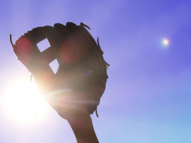 野球の野球のグローブの隙間から見える太陽の写真