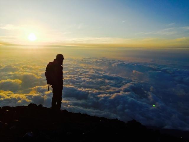 山頂から雲を雲を見下ろす男性の写真