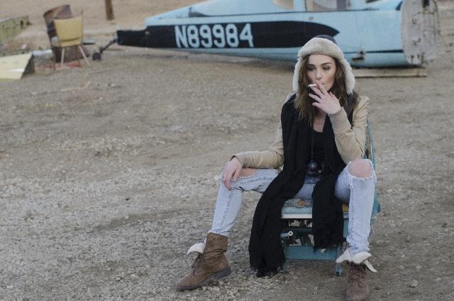 飛行機のオブジェの前でタバコをふかす女性の写真