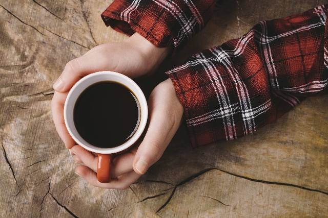 コーヒーカップを持つ女性の手の写真