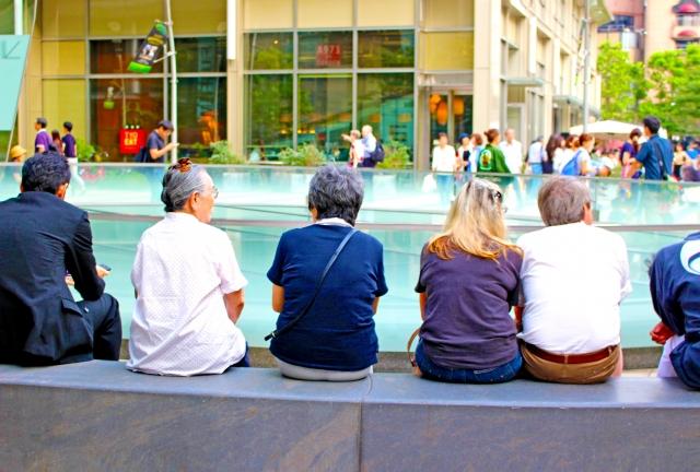 ベンチに座っている人たちを後ろから撮った写真
