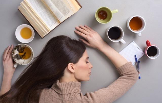 テーブルの上に頭をのせてうたた寝している女性の写真