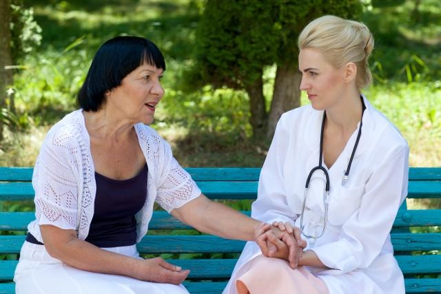 ベンチに座って患者の手を握る医師の写真