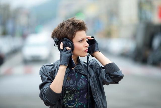 ヘッドホンで音楽を聴いている女性の写真