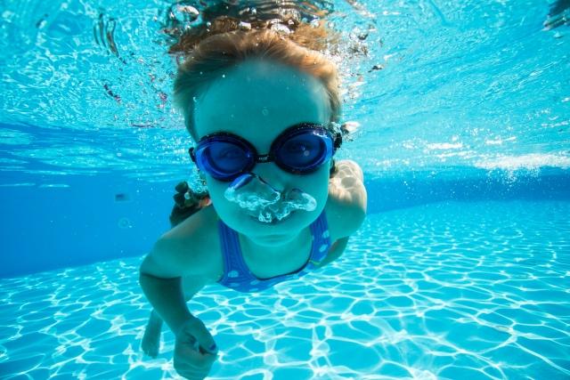 プールで泳ぐ子供の水中写真