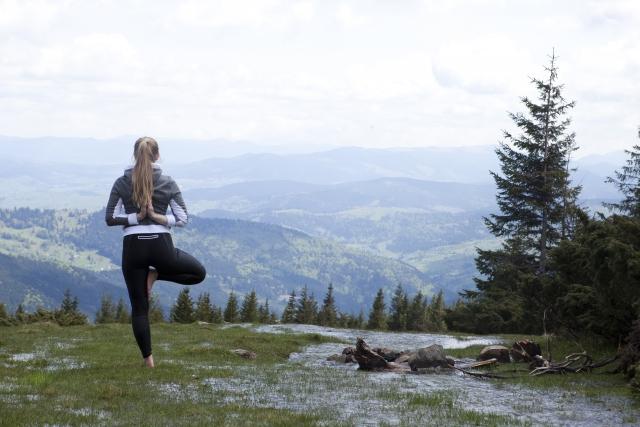 山頂でヨガをしている女性の写真