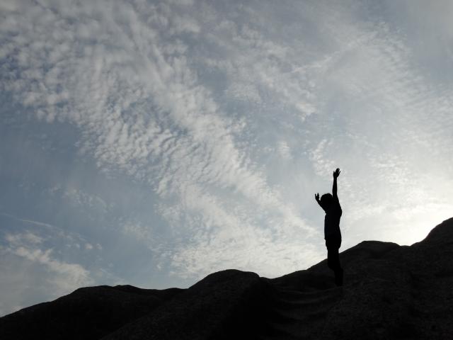 空に向かって手を伸ばしている人の写真