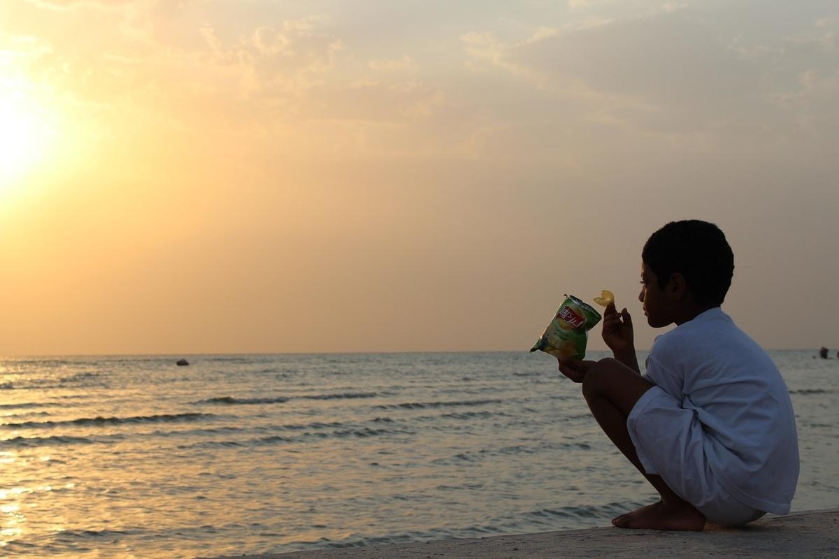 夕日を見つめながらスナック菓子を食べる子どもの写真