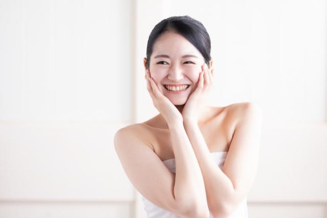 自分の顔の肌を触って微笑む女性