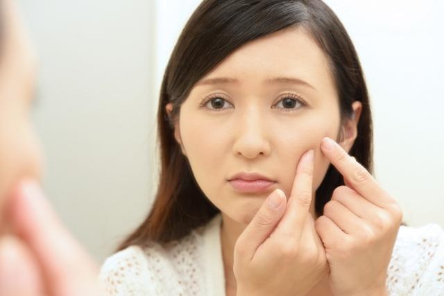 顔の肌を押さえる女性