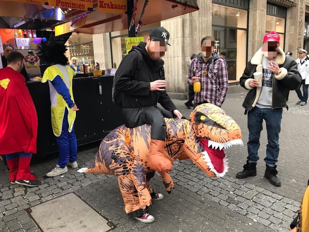 恐竜に乗ってる人の仮装をするドイツ人