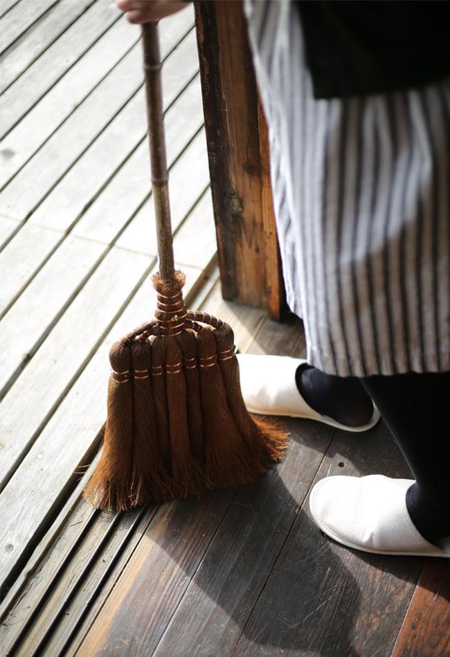 縁側を棕櫚の箒で掃除
