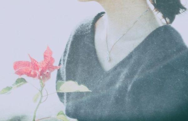 赤い花を持った黒い服の女性