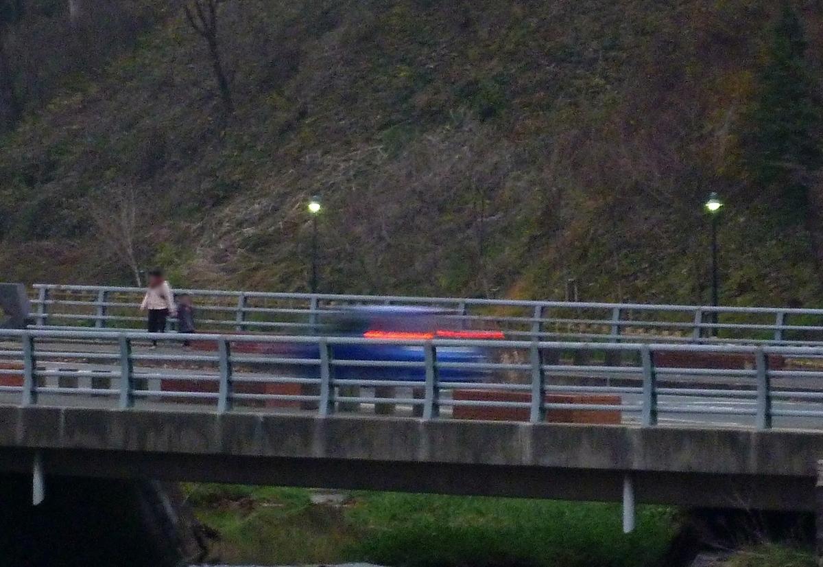 夕刻の橋の上 青い車のテールランプ