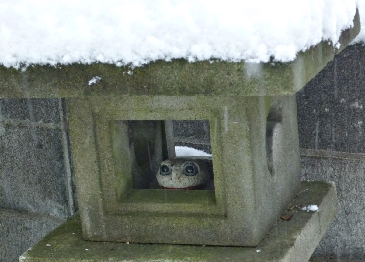 雪が積もった石灯籠と石のカエル