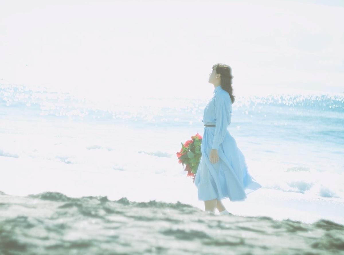 海辺と花を持った女性