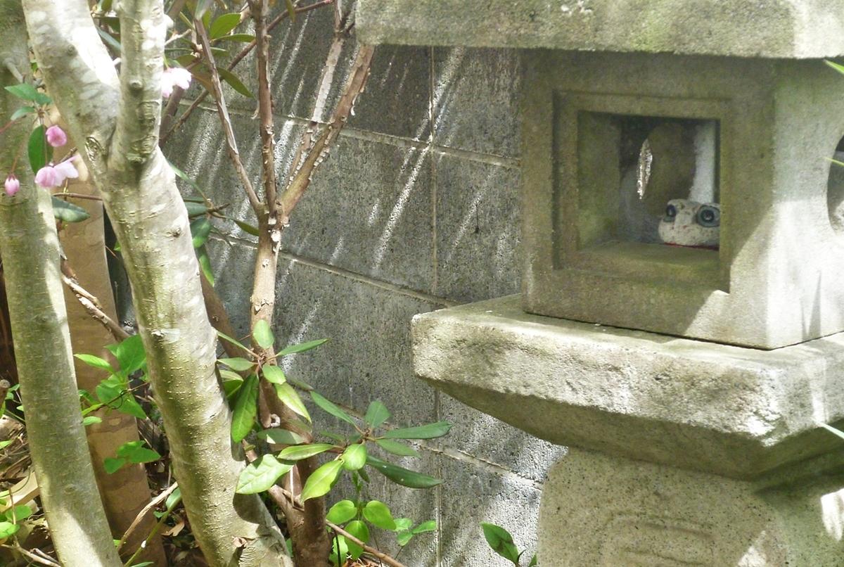 石灯篭とカエルの置物と八重桜の幹
