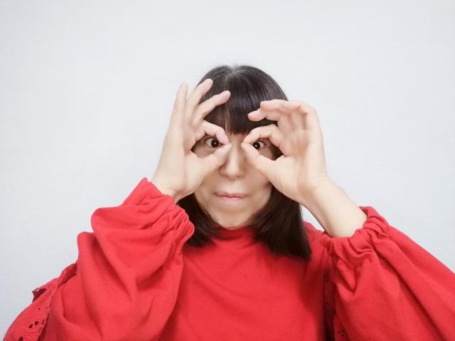 手で眼鏡を作った女性の画像です