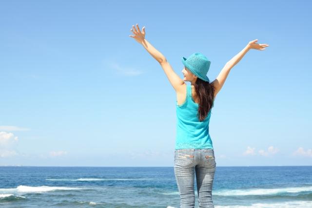 海と伸びをしている女性の画像です