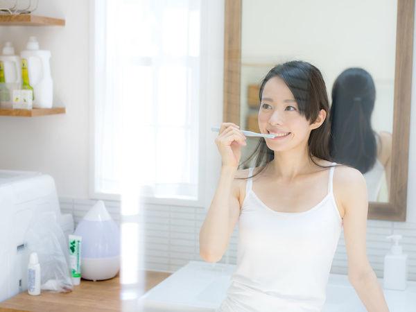 歯磨きをして口臭対策をしている女性