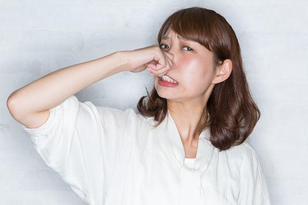足の匂いに耐えきれず鼻をつまむ女性