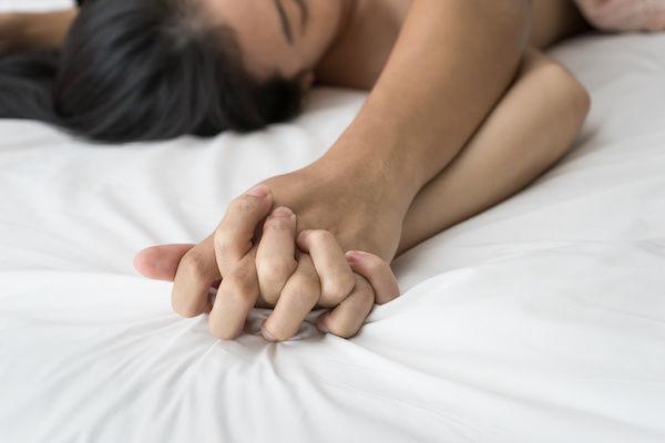 締まりがよくなる体位を試すカップルの手