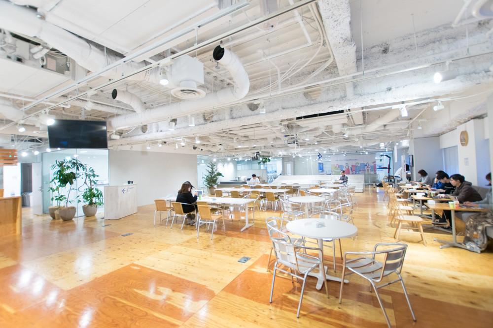 オフィスのイベントスペースの写真。広い空間で、仕事をしている人もいる