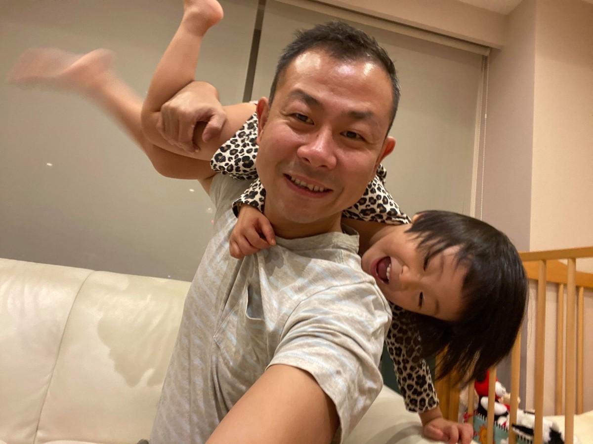 家で子供と遊ぶ筆者。娘を肩の上に担いでいる。