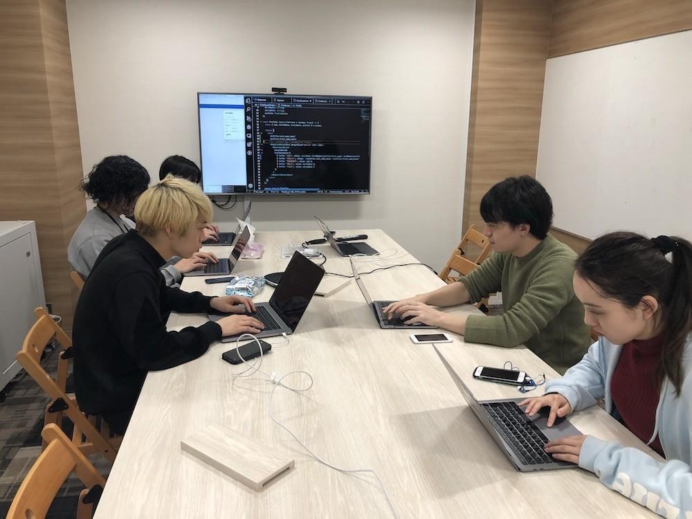 参加者の様子。会議室の机に向かって作業している。正面の大きいモニターには手本となるコードが表示されている