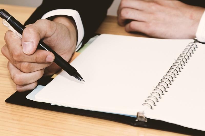 手帳に予定を書き込む男性の手