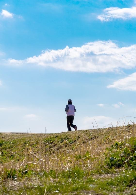 晴れた河川敷を走る男性