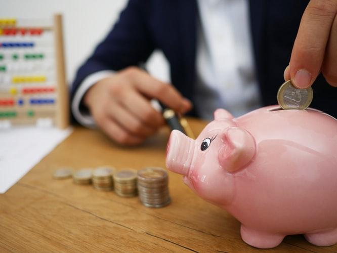 豚の貯金箱にお金を入れているところ