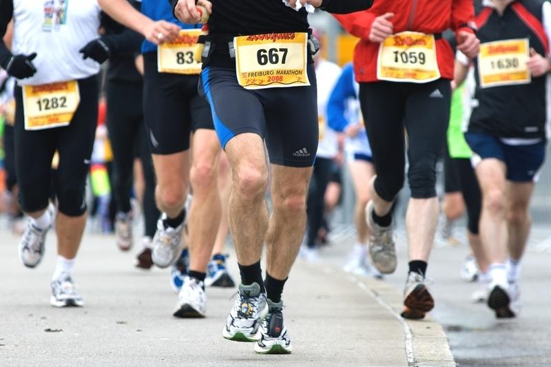 マラソン大会で走っている人たちの足の写真