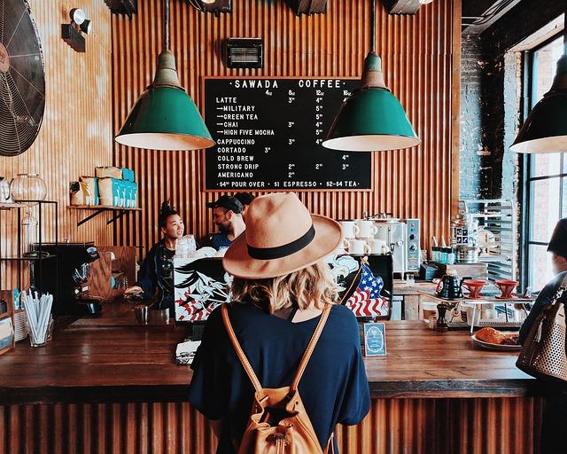 インダストリアルで男前インテリアなカフェに立つ女性