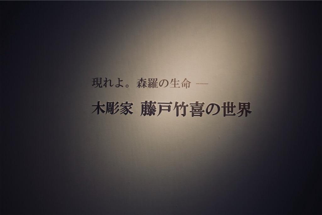 『現れよ。森羅の生命― 木彫家 藤戸竹喜の世界』と書かれた会場の入口