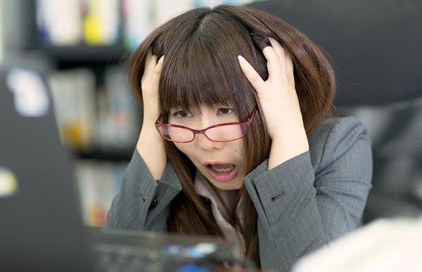 頭を抱えるOL女性社員の画像
