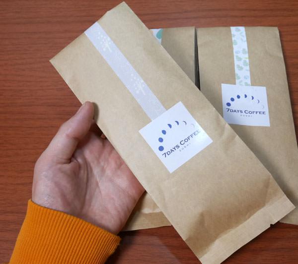 コーヒー豆100gの袋を手に持った大きさ