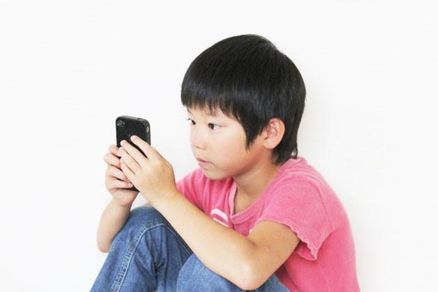 子供がスマートフォンを使っている画像