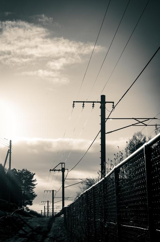 砂利道から線路沿いに立ち並ぶ電線とを撮影しました。電線の向こうに広がる空は流れる雲と朝日が、とてもドラマチックです。