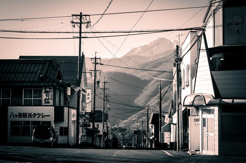 遠くに南アルプス連峰を望む長野県信濃境駅の駅前風景です。やや赤みがかったモノクロ写真に仕上げました。